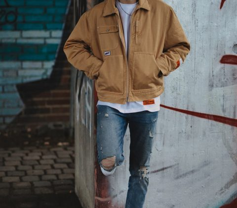 man standing against wall with jacket